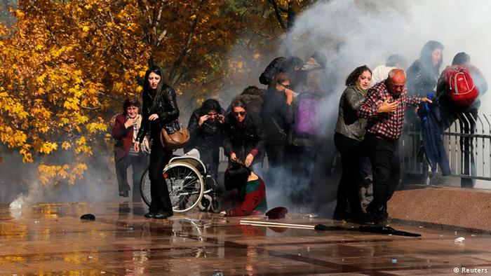 Protesters stand after tear gas was shot toward them during a protest in front of a courthouse in Ankara October 28, 2013. Turkish police fired water cannon and teargas on Monday to break up a protest by around 2,000 people outside the court over the handling of the trial of a policeman accused of killing a demonstrator earlier this year. Officer Ahmet Sahbaz is accused of killing Ethem Sarisuluk, shot dead in June during a wave of nationwide anti-government demonstrations set off by a tough police response to a protest over the redevelopment of a park in Istanbul. REUTERS/Umit Bektas (TURKEY - Tags: POLITICS CIVIL UNREST CRIME LAW TPX IMAGES OF THE DAY)