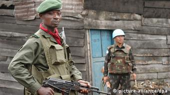 A Congolese soldier guards a street while a UN soldier looks on. EPA/RICKY GARE +++(c) dpa - Report+++