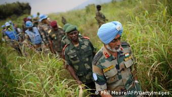 GettyImages 148159489 Brigadier-General Harinder Singh, the United Nations brigade commander for North Kivu (Front R), is followed by General Lucien Bahuma (C), the new commander of the Armed Forces of the Democratic Republic of the Congo (FARDC) for North Kivu, following a strategy meeting above the village of Kibumba I, around 20km from the city of Goma in the Democratic Republic of the Congo's restive North Kivu province on July 11, 2012. The FARDC has deployed forces around Goma to repel any possible advance by M23 rebels on the provincial capital Goma. AFP PHOTO/PHIL MOORE (Photo credit should read PHIL MOORE/AFP/Getty Images)