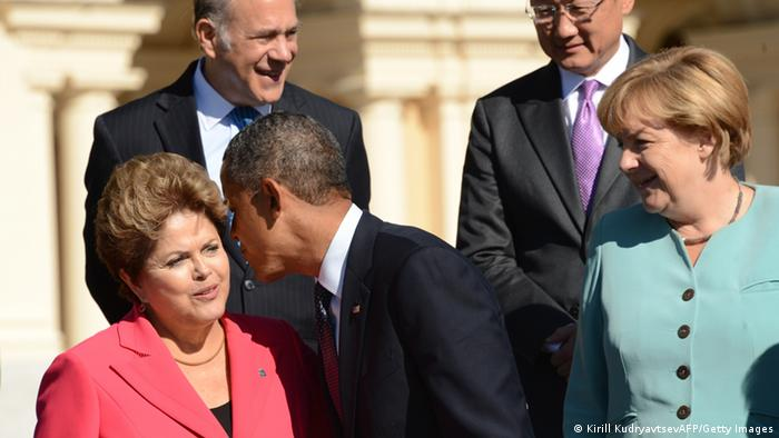 Brazils President Dilma Rousseff (L) is kissed by US President Barack Obama (C) as Germany's Chancellor Angela Merkel looks on (R)