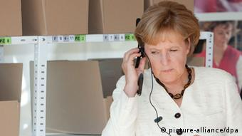 Chancellor Merkel in a white suit concentrating on listening to an earpiece