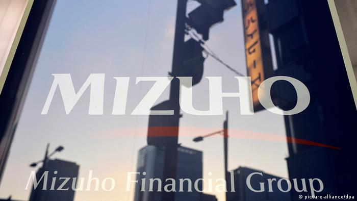 epa03928018 Buildings are reflected in a Mizuho Financial Group Inc. sign in Tokyo, Japan, 28 October 2013. Japan_s Mizuho Financial Group Inc said it had punished a total of 54 current and former executives over its loans to organized crime groups, but a third-party panel found no sign of a deliberate cover-up. Mizuho Bank president Yasuhiko Sato said his salary would be cut for six months and other executives would step down from their posts or face pay reductions. The scandal surfaced in late September when Japan_s second-largest bank by assets was ordered to clean up its operations following an inspection by Japan_s Financial Services Agency. EPA/FRANCK ROBICHON