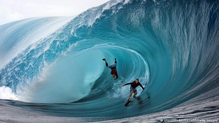 Two surfers ride a massive wave