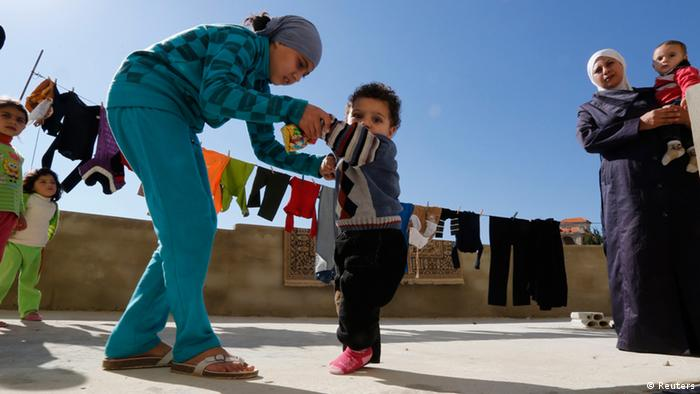A Syrian refugee girl helps her brother, who the family suspects has polio, to walk as their mother watches in a mosque compound in Shebaa area, southern Lebanon October 28, 2018. Around 400 Syrian refugees live within the mosque compound, according to the municipality of Shebaa area, where more than 4,000 Syrian refugees live. Roughly 750,000 Syrian refugees are in Lebanon according to U.N. figures. It predicts that number will rise to 1.3 million by January and to 1.6 million, or 37 percent of the country's pre-crisis population, by the end of next year. Picture taken October 28, 2013. REUTERS/ Jamal Saidi (LEBANON - Tags: POLITICS CIVIL UNREST CONFLICT)