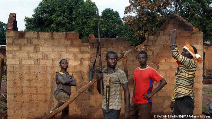 Young people patrol with rifles near a house destroyed by fire on October 11, 2013 in Bogangolo (171 km from Bangui). The Central African Republic, one of the poorest countries on the planet with a long history of instability, has descended into anarchy since rebels overthrew president Francoise Bozize in March 2013. Violence has surged between ex-rebels of the Seleka coalition that led the coup -- who are Muslim -- and local vigilante groups formed by Christian residents in rural areas. AFP PHOTO / PACOME PABANDJI (Photo credit should read PACOME PABANDJI/AFP/Getty Images)