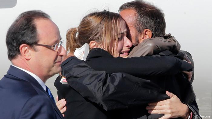 Former French hostage Daniel Larribe (R) is welcomed by relatives next to French President Francois Hollande (L) on the tarmac upon their arrival at Villacoublay military airport, near Paris, October 30, 2013. Four Frenchmen Pierre Legrand, Daniel Larribe, Thierry Dol and Marc Feret held hostage in the Sahara desert by al Qaeda-linked gunmen for three years left Niger on a French government plane on Wednesday morning. The men, who were kidnapped in 2010 while working for French nuclear group Areva and a subsidiary of construction group Vinci in northern Niger, were freed on Tuesday after secret talks. REUTERS/Jacky Naegelen (FRANCE - Tags: POLITICS TPX IMAGES OF THE DAY)