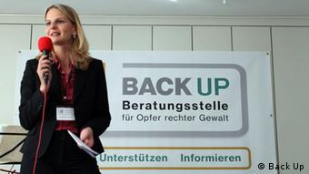 A blonde-haired woman wearing a dark business suit holds a microphone on a podium with a sign behind her that reads Back Up.