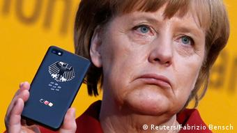 Angela Merkel, frowning, holds up a smartphone