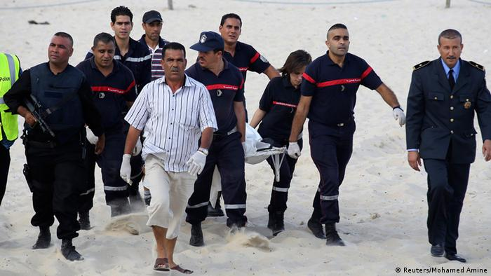 Police officers carry the body of a suicide bomber from the crime scene at a beach near the tourist resort of Sousse October 30, 2013. The suicide bomber blew himself up without causing other casualties, security sources said. REUTERS/Mohamed Amine ben Aziza