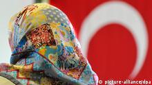 Ein Frau mit Kopftuch sitzt am Samstag (22.05.2010) in der DITIB-Moschee im hessischen Friedberg vor einer türkischen Fahne. In seiner Funktion als Integrationsminister besuchte der hessische Vize-Ministerpräsident Hahn (FDP) am Pfingstsamstag die Gemeinde, um sich über den interkulturellen Dialog zwischen Deutschland und der Türkei sowie den Stand eines Aufklärungsprojekts für Imame zu informieren. Foto: Boris Roessler dpa/lhe (zu dpa/lhe 7119)