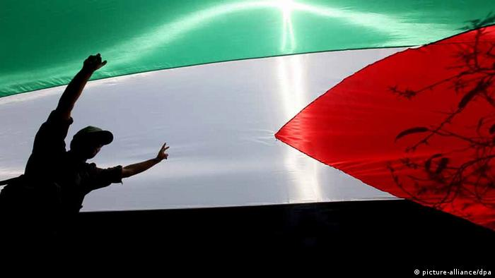 Palestinian Hamas security walk under a large Palestinian flag during a rally (photo: EPA/MOHAMMED SABER)