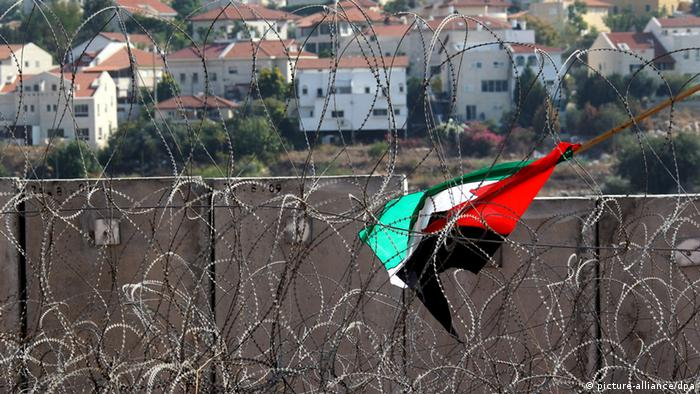 A Palestinian flag lies amid rolls of barb wire after it was discarded at the end of a protest against the israeli 'separation barrier' or wall in the West Bank village of Ni'lin on 12 November 2010 (Photo: EPA/JIM HOLLANDER)