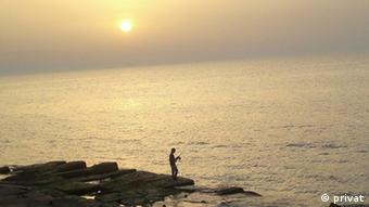 A fisherman against the backdrop of the sea at sunset