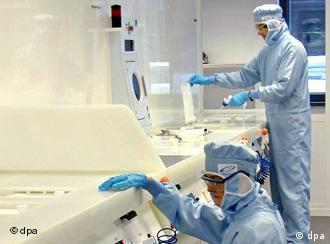 Two scientists in protective suits perform their work in a laboratory