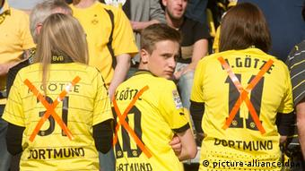 Fans show the crossed out Dortmund jersey of Mario Götze. Foto: Bernd Thissen/dpa