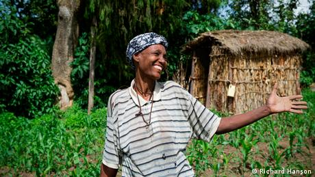 Tirame stands beaming in front of her latrine, an outdoor wooden hut