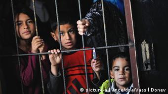 Kinder schauen durch einen Gitterzaun (Foto: picture-alliance/dpa/Vassil Donev)