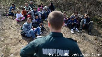 Ein bulgarischer Polizist schaut auf Flüchtlinge (Foto: picture-alliance/dpa/Vassil Donev)