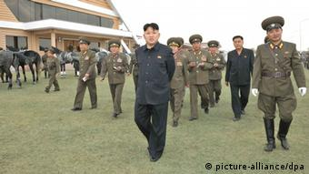 An undated picture released by the North Korean Central News Agency (KCNA) on 22 October 2013 shows North Korean leader Kim Jong-un (C) touring the Mirim Riding Club (Photo: EPA/KCNA)