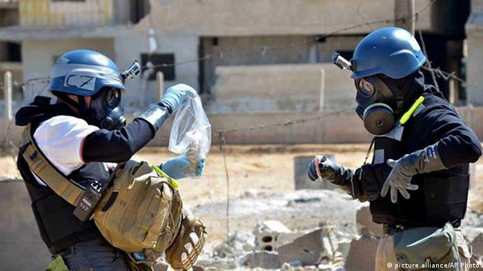 FILE - In this Wednesday, Aug. 28, 2013 citizen journalism image provided by the United media office of Arbeen which has been authenticated based on its contents and other AP reporting, members of the UN investigation team take samples from sand near a part of a missile that is likely to be one of the chemical rockets according to activists, in the Damascus countryside of Ain Terma, Syria. Russia's proposal to place Syria's chemical weapons stockpile under international control for dismantling would involve a lengthy and complicated operation made more difficult by a deep lack of trust. Syria is believed by experts to have 1,000 tons of chemical warfare agents scattered over several dozen sites across the country, and just getting them transferred while fighting rages presents a logistical and security nightmare. (AP Photo/United media office of Arbeen)