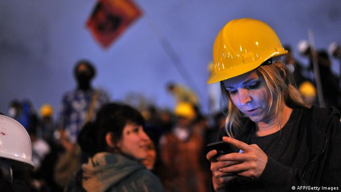 A Turkish woman using a mobile phone to read the news on social media joins demonstrators at midnight in Taksim Gezi Park (photo: OZAN KOSE/AFP/Getty Images)
