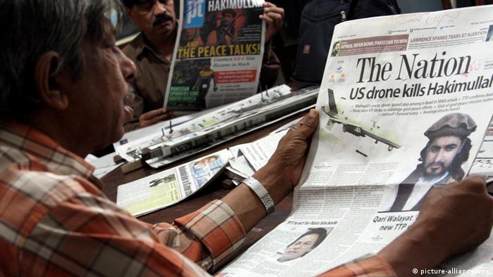 Pakistani men read newspapers carrying front-pages about the death of Hakimullah Mehsud (Photo: EPA/REHAN KHAN)