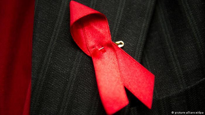 Eine rote Aids-Schleife steckt am Anzug eines Mannes - Foto: Jan-Philipp Strobel (dpa)