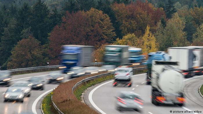 Lorries and cars drive on the Autobahn, the German motorway, with a backdrop of trees in Autumn colors. (Photo: Armin Weigel/dpa)