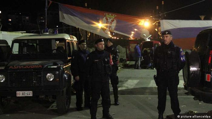 Armed security forces dressed in black stand on a stree during the night time.