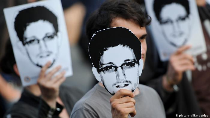 Demonstrators with cut out faces of Edward Snowden in Berlin. Photo: Ole Spata/dpa