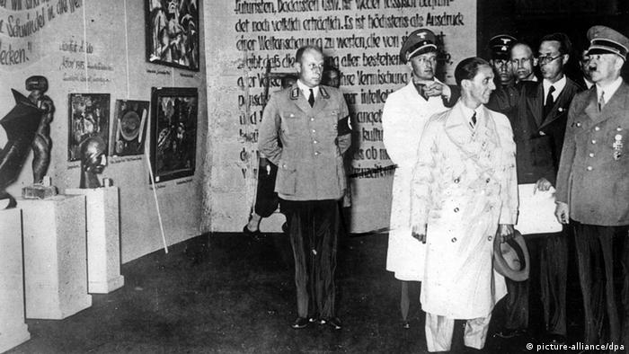 In a black-and-white image from 1937, Hitler and Goebbels visit an art exhibit, where old German script is written on a wall.