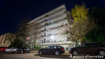 A modern gray apartment building flanked by trees is underlit and contrasts against a dark sky.