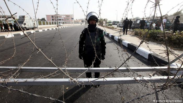 epa03935312 A riot police officer stands guard behind barbed wire during the first day of the trial of ousted Egyptian President Mohamed Morsi, outside the Egyptian police academy in Cairo, Egypt, 04 November 2013. Egypt's toppled Islamist president, Mohammed Morsi, arrived on 04 November at the venue where his trial on charges of inciting the killing of opposition protesters is due to open. EPA/KHALED ELFIQI