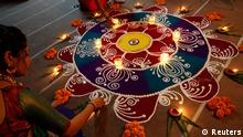 Hindu women arrange oil lamps and flowers around a Rangoli, a traditional pattern made from coloured powders, during the celebrations ahead of the Hindu festival of Diwali in the western Indian city of Ahmedabad November 1, 2013. Diwali, the annual festival of lights will be celebrated across the country on November 3. REUTERS/Amit Dave (INDIA - Tags: RELIGION SOCIETY)