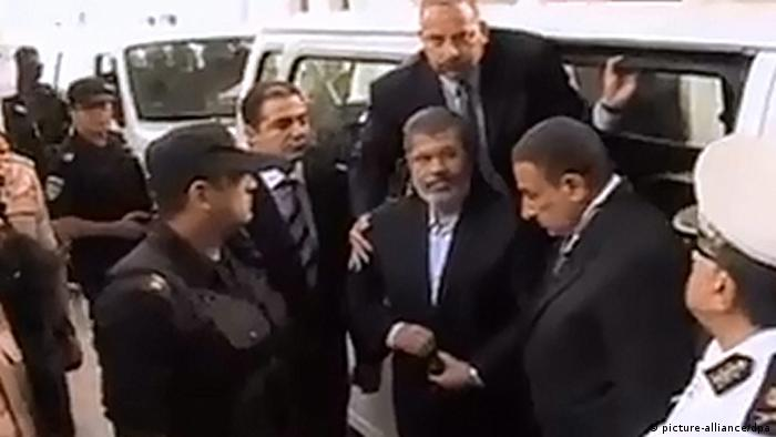 epa03935720 A grab made of video released by the Egyptian interior ministry showing ousted president Mohamed Morsi (C) arriving for his first trial session, in Cairo, Egypt, 04 November 2013. Egypt's toppled Islamist president, Mohammed Morsi, arrived on 04 November at the venue where his trial on charges of inciting the killing of opposition protesters is due to open. The so-called 'four-finger salute' has come to symbolize the lives lost during the dispersal of the Rabaa al-Adawiya protest camp by the Egyptian army. EPA/INTERIOR MINISTRY HANDOUT BEST QUALITY AVAILABLE HANDOUT EDITORIAL USE ONLY/NO SALES pixel
