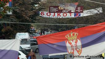 Kosovar Serbs are passing by Serbian flags and slogans which invite people to boycott local elections in Kosovo, in the northern part of ethnically divided town of Mitrovica, Kosovo, 01 November 2013. Kosovo holds municipal elections on 03 November that will test its recently improved ties with Serbia. The two neighbours in April 2013 reached an EU-brokered deal to normalize relations after Albanian-majority Kosovo declared independence from Serbia in 2008. Under the deal, Serbia agreed to scale back its influence in Serb-majority areas in northern Kosovo. EPA/DJORDJE SAVIC +++(c) dpa - Bildfunk+++