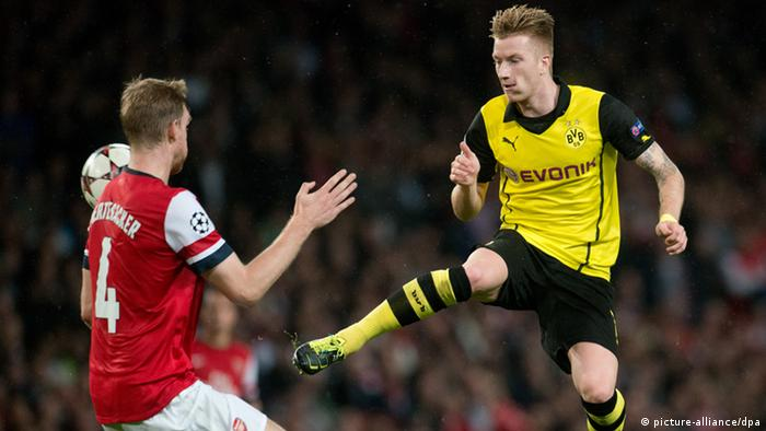 Arsenals Per Mertesacker and Dortmunds Marco Reus kämpfen im Hinspiel um den Ball. Foto: dpa
