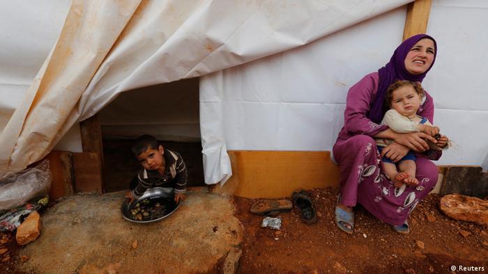 Eine syrische Frau mit ihrem Säugling vor einem Flüchtlingszelt (Foto: rtr)