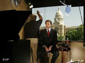 Texas Gov. Rick Perry, seated, prepares to tape a public service message about preparation in advance of hurricane Rita on Tuesday, Sept. 20, 2005, in Austin, Texas. Ray Guy, left, adjusts a filter over the window that faces the Texas Capitol. Rita strengthened into a hurricane as it lashed the Florida Keys with heavy rain and strong wind. It sparks fears that the storm could eventually bring new misery to the Gulf Coast. (AP Photo/Harry Cabluck)