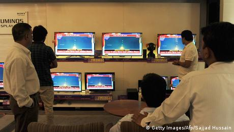 Indian bystanders watch a bank of screens showing the live telecast of the launch of India's Mars Orbiter Mission inside a showroom in New Delhi on November 5, 2013. (Photo: SAJJAD HUSSAIN/AFP/Getty Images)