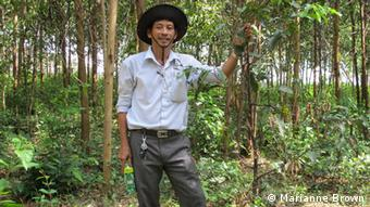 PHOTO INFO Title: Vietnam Xuyen 2 Keywords: Vietnam Timber Who is the photographer: Marianne Brown When was the picture taken: September 24 Where was the picture taken: Quang Nam province, Vietnam Description: What are we seeing in this picture? Who are we seeing? Plantation farmer Le Xuyen stands near the road in a copse of acacia trees in the plantation he manages in central Vietnam.