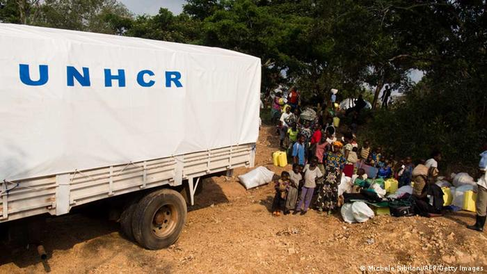 A group of people waiting next to a UNHCR truck containing aid materials