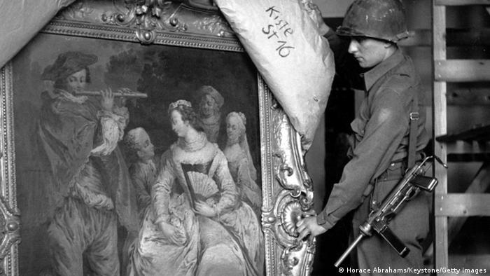 Black-and-white photo of a soldier pulling back a covering over a stolen Fragonard painting