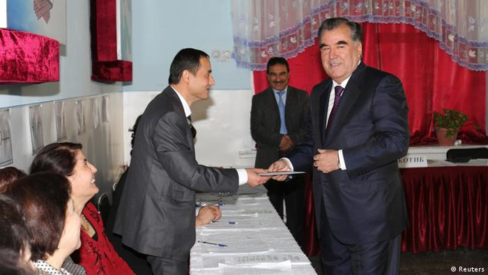 Tajikistan's President Imomali Rakhmon (R) receives his ballot from an electoral official during the presidential election in Dushanbe, in this November 6, 2013 handout photograph provided by Press Service of presidential administration of Tajikistan. Tajikistan on Wednesday started voting in a presidential election in which incumbent Rakhmon is set to win a new seven-year term to lead the Central Asian country that faces security threats from neighboring Afghanistan. REUTERS/Press Service of presidential administration of Tajikistan/Handout via Reuters (TAJIKISTAN - Tags: POLITICS ELECTIONS) ATTENTION EDITORS - THIS IMAGE WAS PROVIDED BY A THIRD PARTY. FOR EDITORIAL USE ONLY. NOT FOR SALE FOR MARKETING OR ADVERTISING. THIS PICTURE IS DISTRIBUTED EXACTLY AS RECEIVED BY REUTERS, AS A SERVICE TO CLIENTS