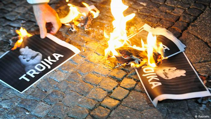 A man burns signs with the word Troika during an anti-austerity and anti-governmental protest in Ljubljana October 29, 2013. REUTERS/Srdjan Zivulovic (SLOVENIA - Tags: POLITICS CIVIL UNREST BUSINESS)