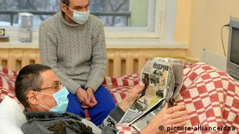 Photo: Two men wearing protective face masks in a tuberculosis clinic. (Photo: ITAR-TASS/ Alexei Ivanov)