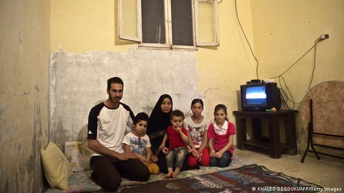 Syrian refugee Yussef al-Talha 29, who works as a computer technician from Deraa in southern Syria, sits with his family, (From L to R) son Mohamed, 5, wife Rem al-Sawaa, 28, son Khaled, 1, daughter Asma,12, and daughter Shayma, 8, at their home in the Helwaan district of the Egyptian capital of Cairo on November 1, 2013. AFP PHOTO / KHALED DESOUKI (Photo credit should read KHALED DESOUKI/AFP/Getty Images) Erstellt am: 01 Nov 2013