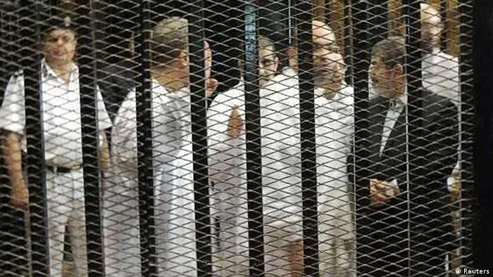 Ousted former Egyptian president Mohamed Mursi (R) speaks with other senior figures of the Muslim Brotherhood in a cage in a courthouse on the first day of his trial, in Cairo, November 4, 2013. Ousted Egyptian leader Mursi, given his first public forum since his overthrow, in a trial where he could face execution, declared on Monday he was still Egypt's legitimate president and shouted: Down with military rule!. It was the first public sighting of Mursi since he was ousted by the army on July 3 after mass protests against his rule. REUTERS/Stringer (EGYPT - Tags: POLITICS CIVIL UNREST CRIME LAW)