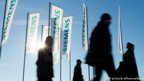 Siemens employees with flags (picture-alliance/dpa)
