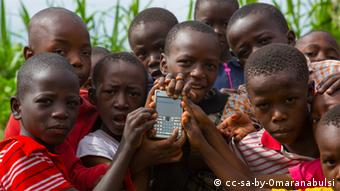 A group of African children holding a mobile phone looks at the camera.